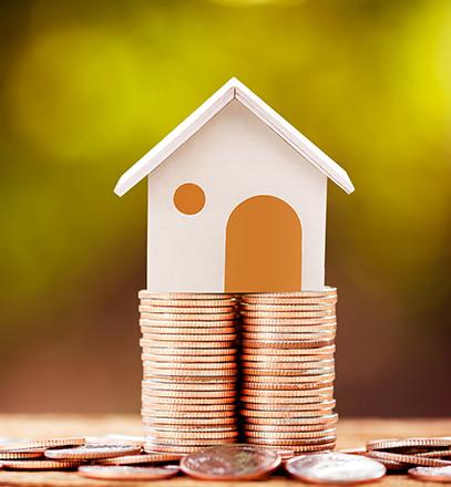 Modell-Haus auf einem Stapel Münzen