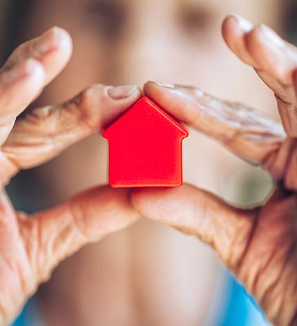 Frau hält rotes Modell-Haus in den Händen