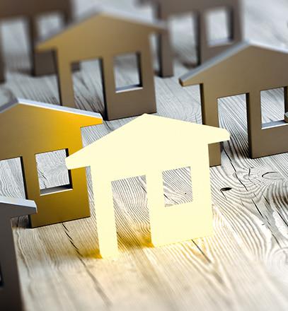 Leuchtende Immobilie zwischen grauen Modell-Häusern