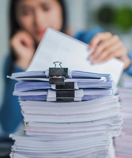 Frau bei der Immobilien-Kalkulation vor einem Stapel Papier